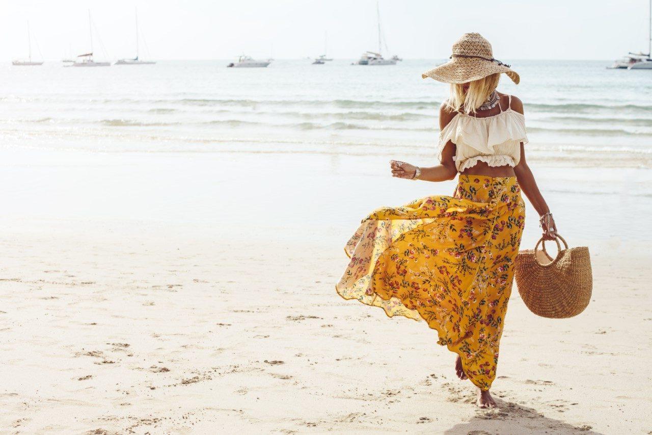 Vrouw met hoed en rok op strand
